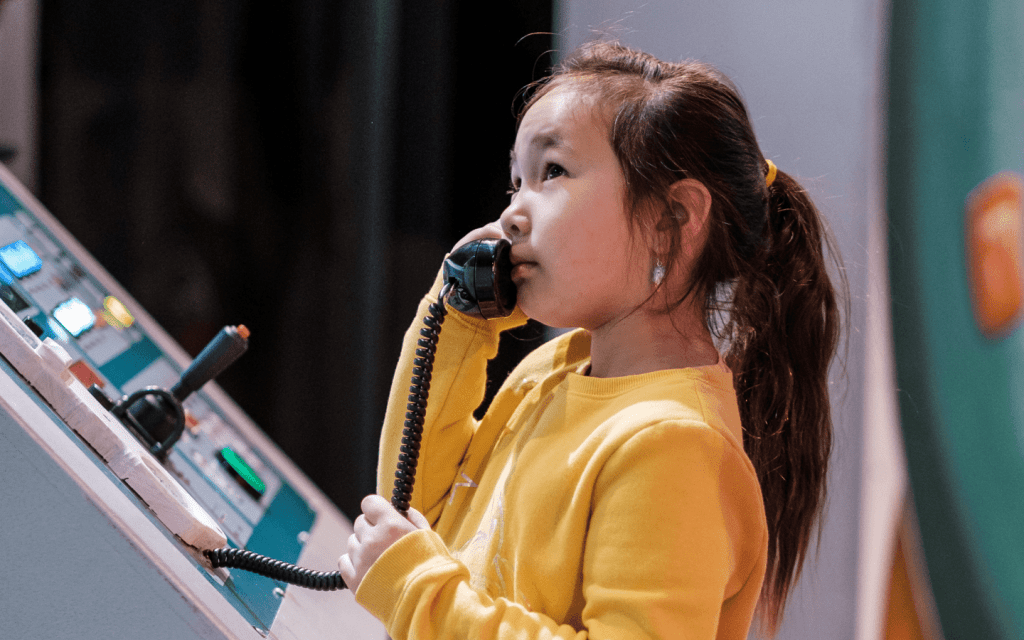 little girl wearing a yellow sweater on the phone