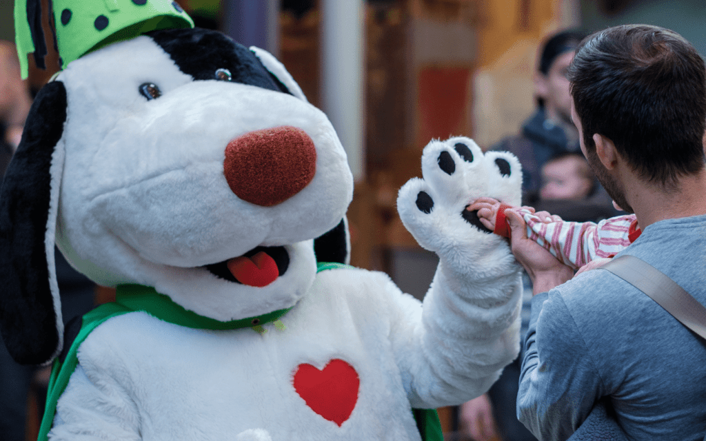 a black and white dog mascot giving a child a high five