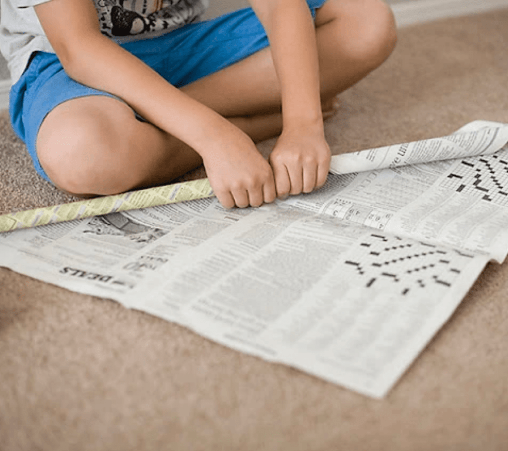 A boy sitting down rolling up newspaper