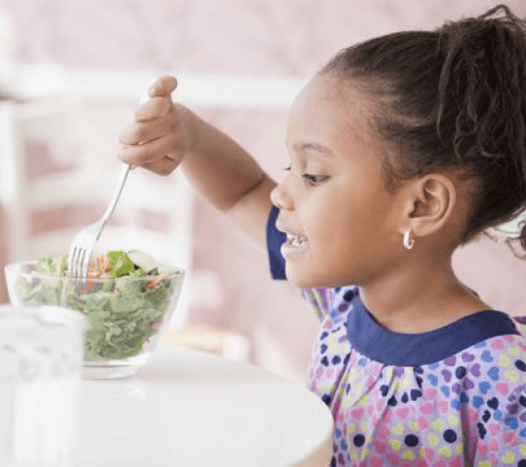 a young girl eating a kale salad