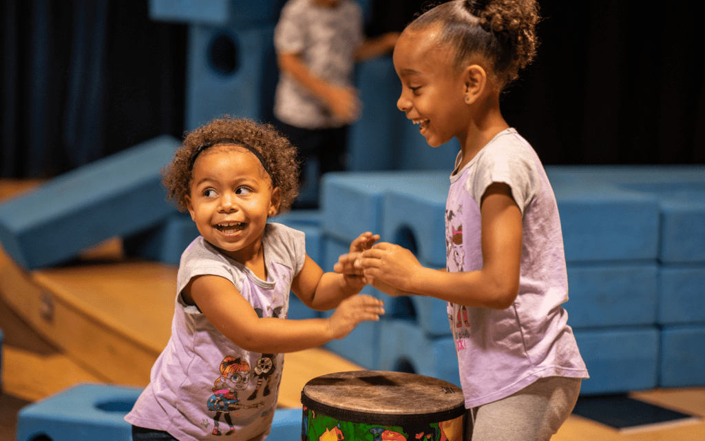 2 young girls playing with a drum and smiling