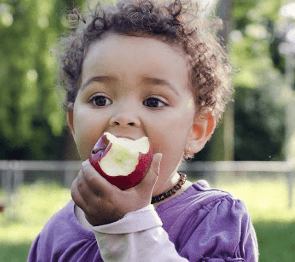 a young girl eating an apple
