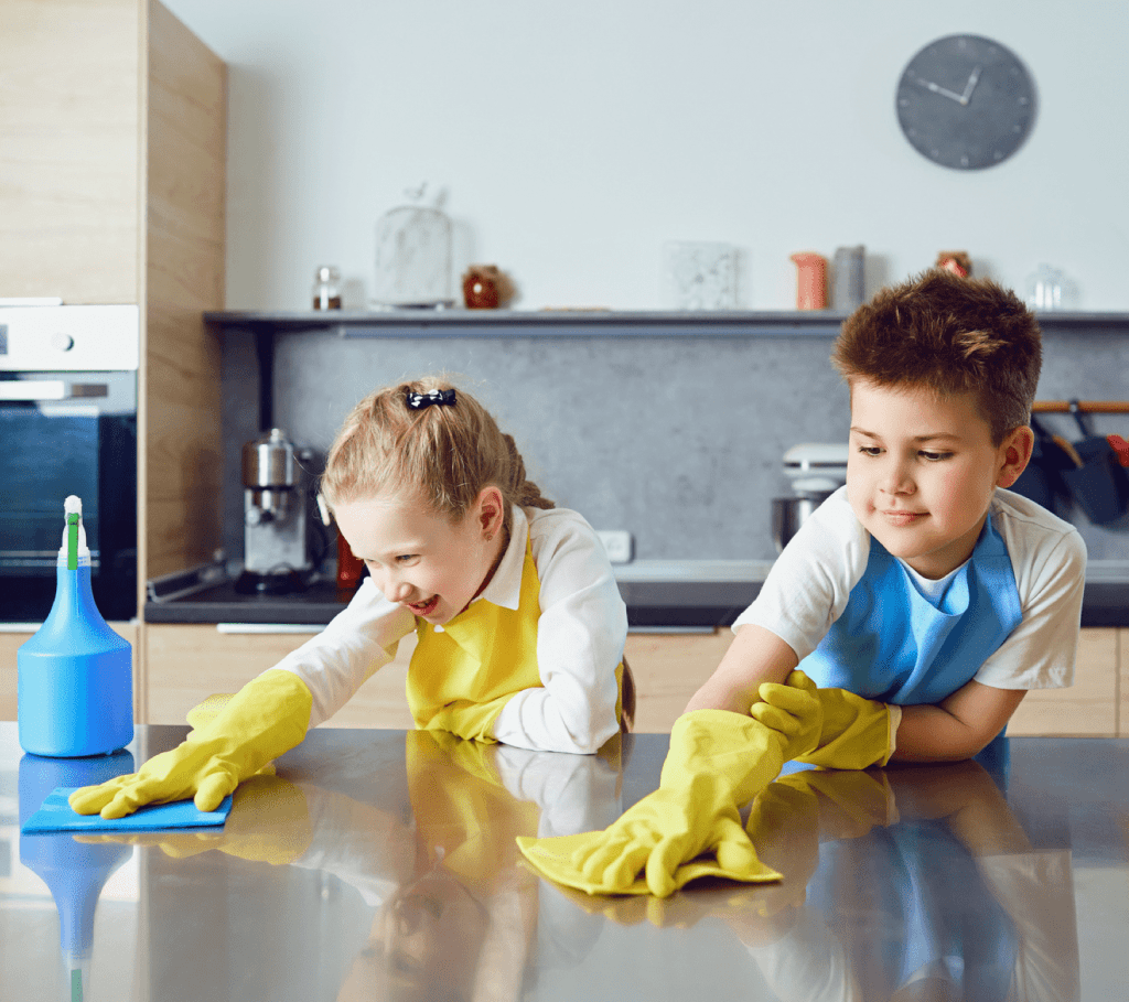 2 young children cleaning a stainless steel surface