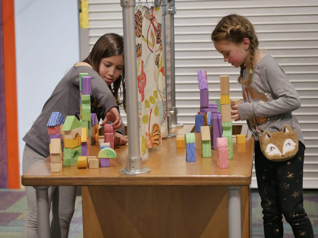 2 girls playing with building blocks