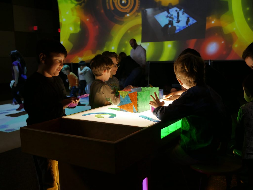 a low lit room with boys playing with light up toys