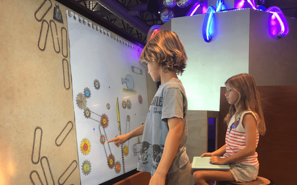 a boy and girl playing with an interactive screen