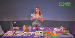 an instructor explaining a cookbook with food