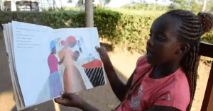 a young kenya girl reading a book