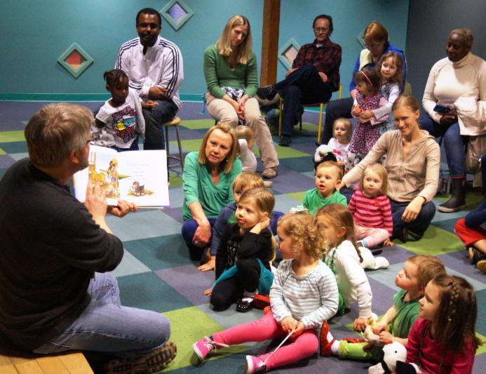 children and parents sitting listening to a book reader