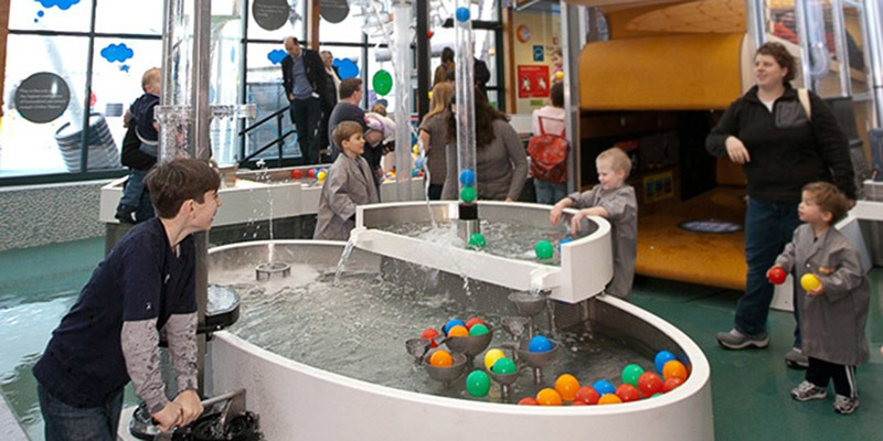 a group of boys playing with plastic balls in water