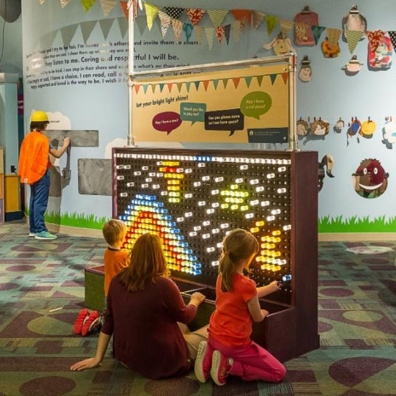 a group of boys and girls playing with a light up display