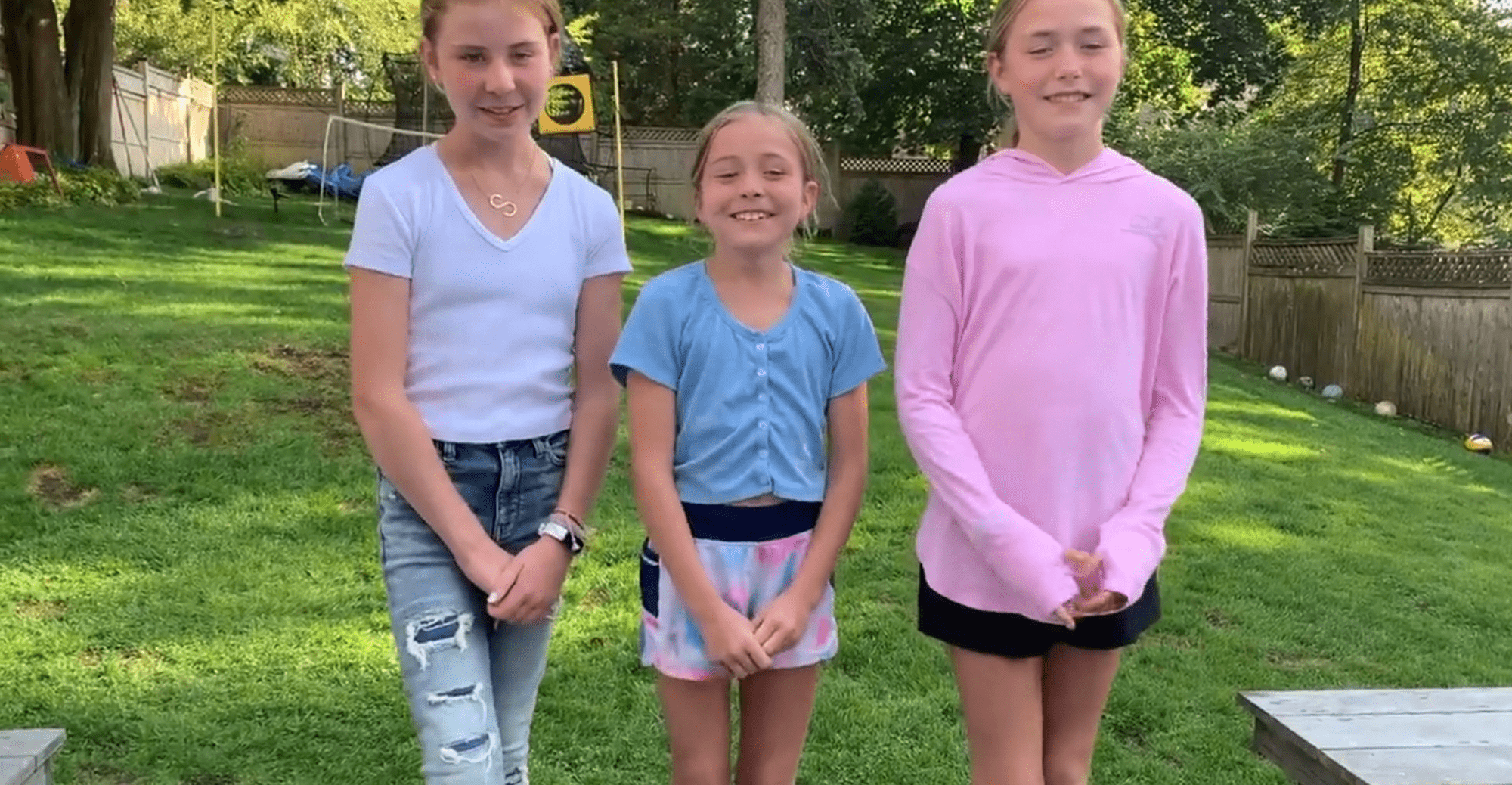 3 young girls smiling standing in their backyard